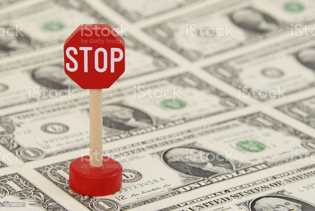 STOP Sign standing on One Dollar Bills stock photo