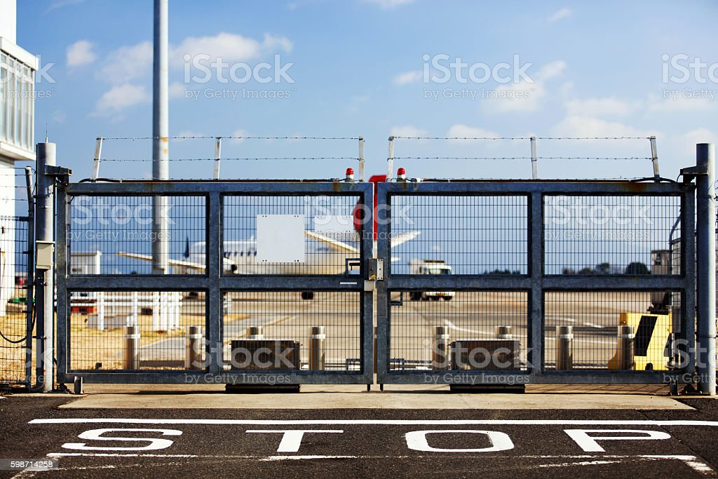 Sign STOP in fron of closed gate in airport stock photo