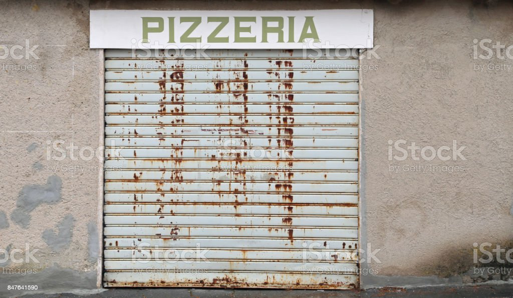 sign with PIZZERIA text with the gate closed because of the econ stock photo