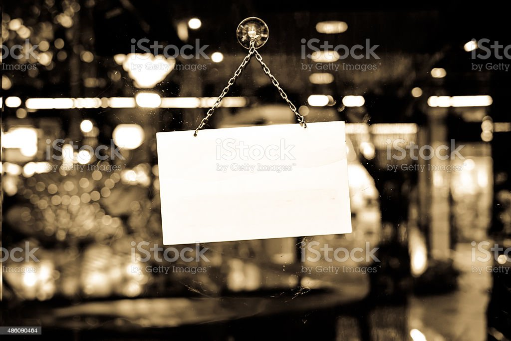 Sign with space for text hanging in a shop window stock photo