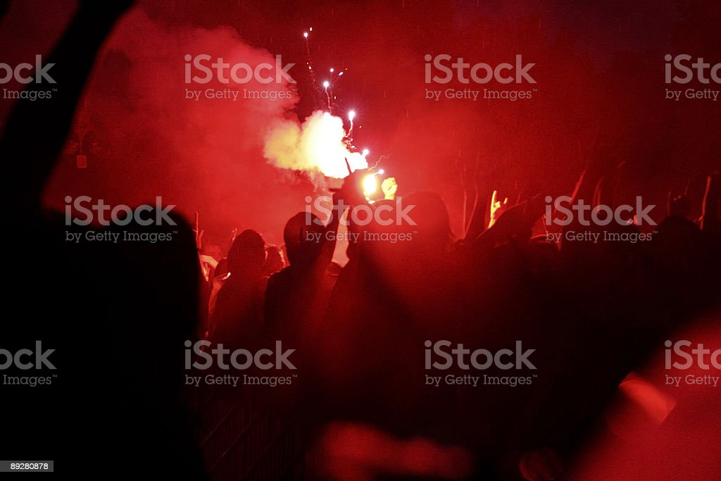 Signal flare in a rioting crowd. stock photo