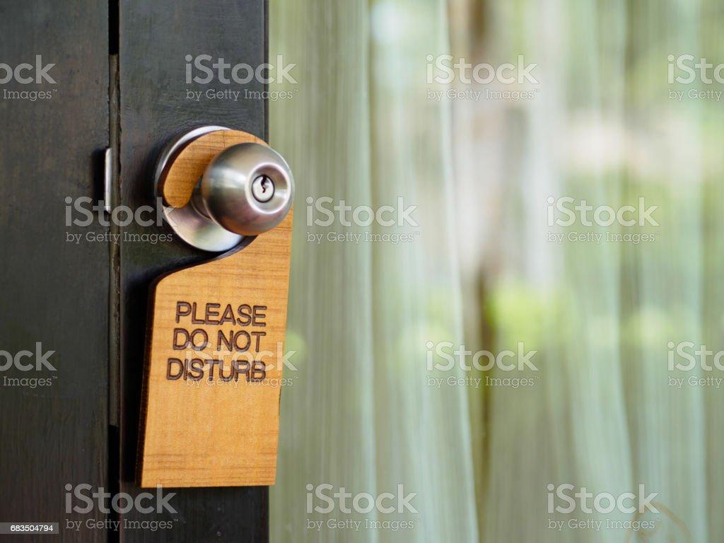 Signboard do not disturb hanging on open door in a hotel stock photo