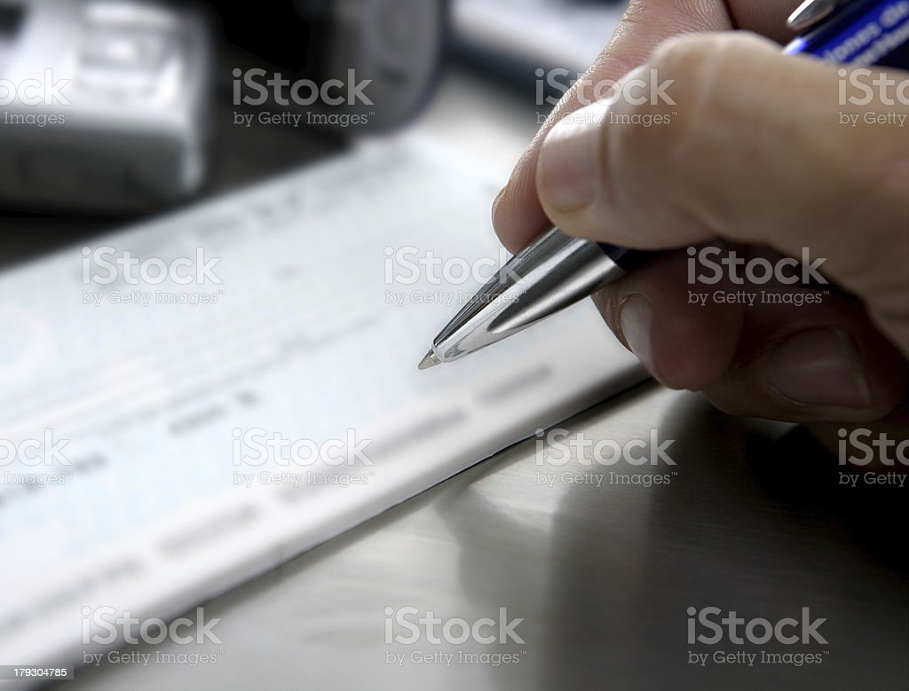 Signing a bank check, business metaphor stock photo