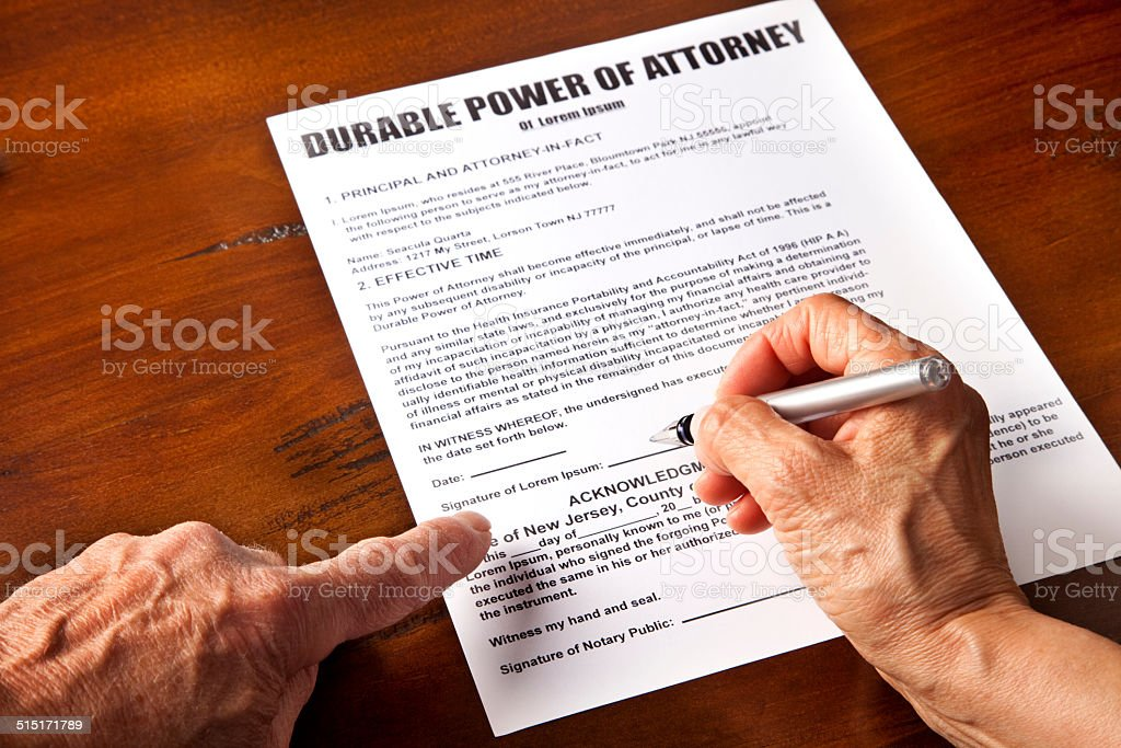 Signing Durable Power of Attorney document, Hands holding pen stock photo