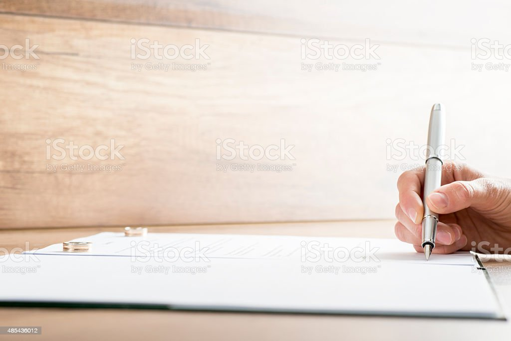 Signing marriage contract or divorce papers stock photo