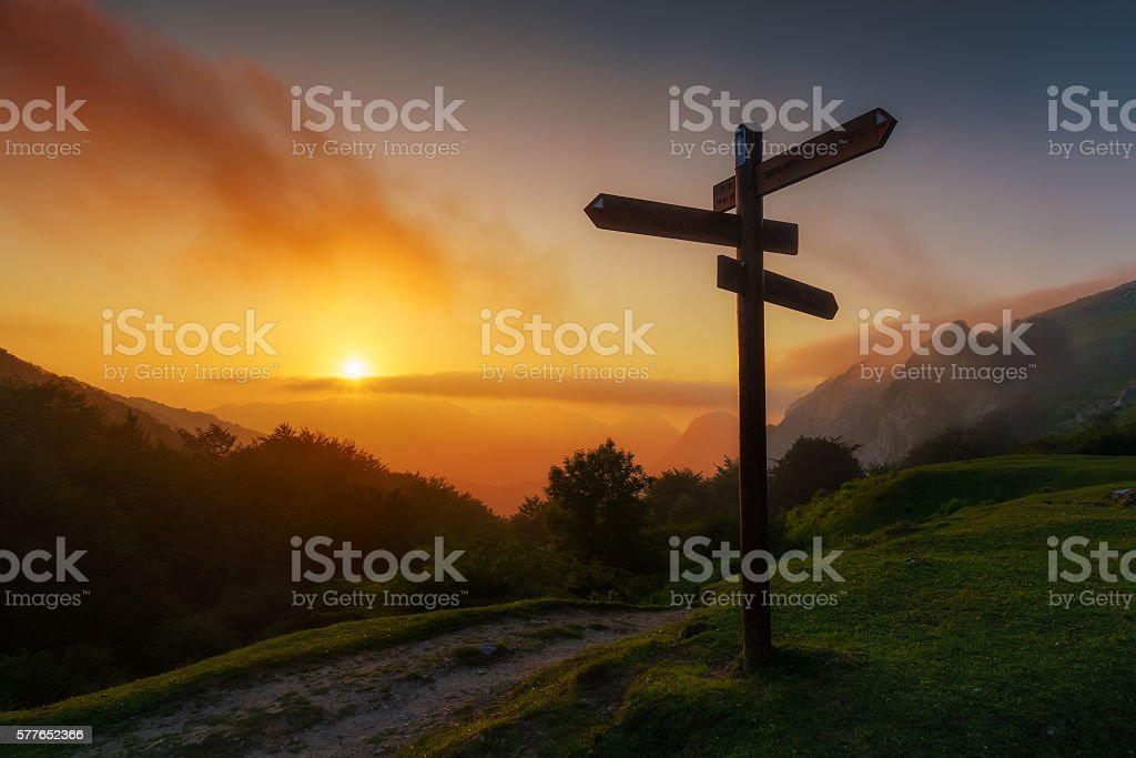 signpost in the mountain at sunset stock photo