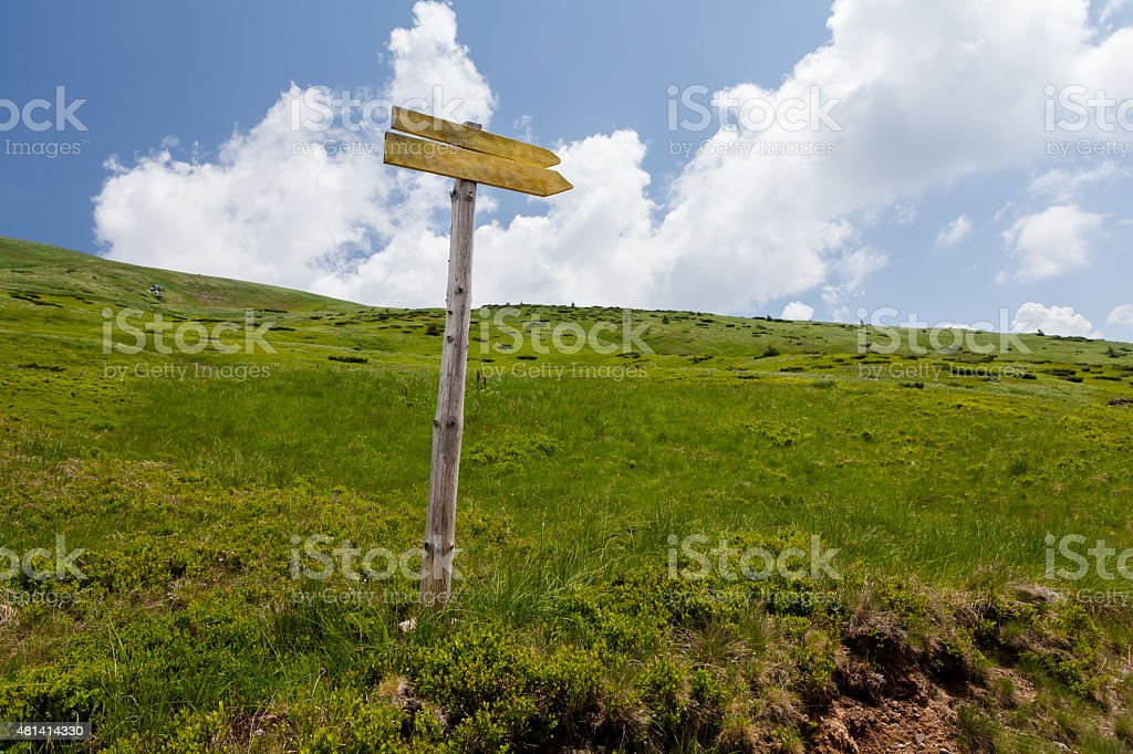 Signpost on trail in front of blue sky stock photo