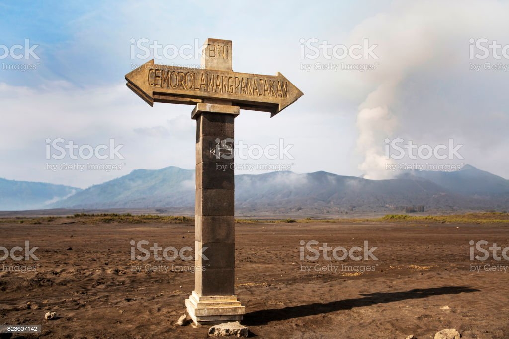 Signposts pointing to the bottom of the volcano caldera. Mt. Bromo volcano during sunrise, the magnificent view of Mt. Bromo located in Bromo Tengger Semeru National Park, East Java, Indonesia stock photo