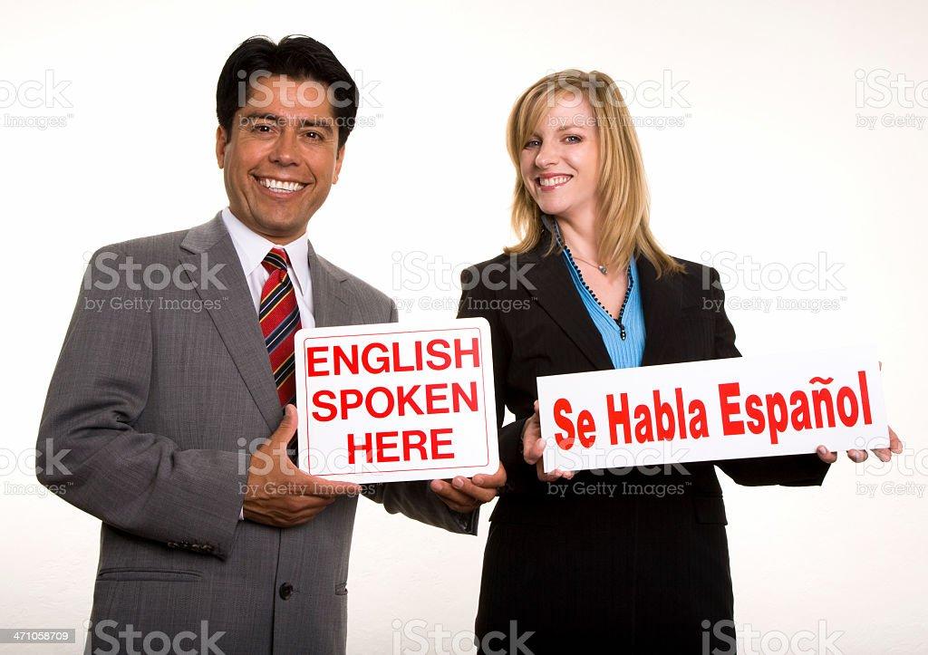 Signs held saying 'English Spoken Here' and 'Se Habla Espanol' stock photo