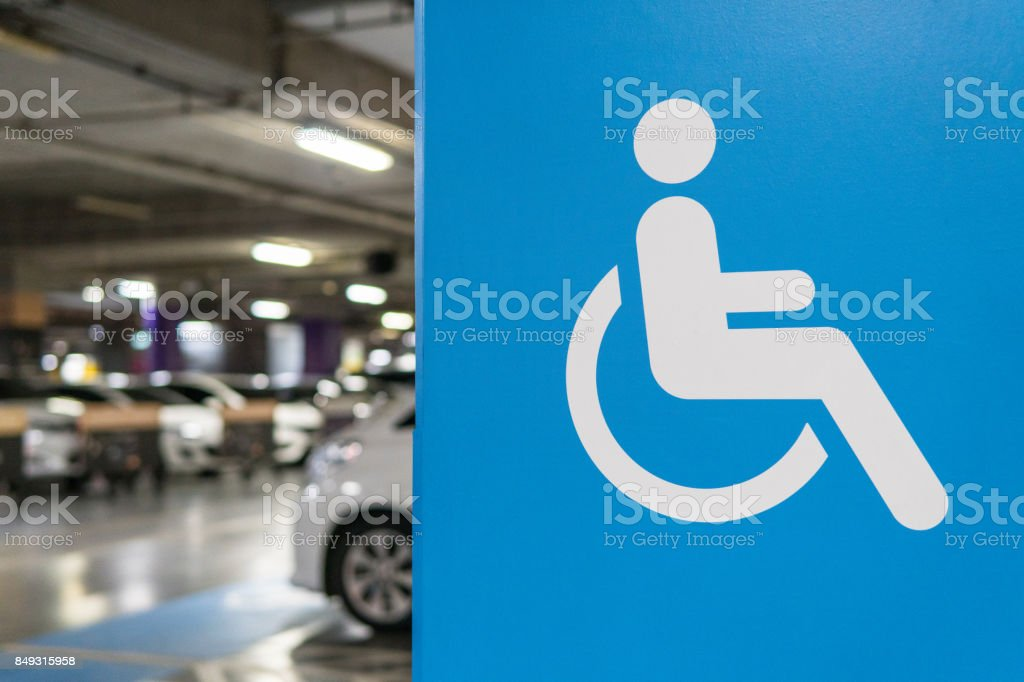 Signs marked disabled parking. In the parking lot of the mall. Currently, there are several shopping centers. Do the parking for the disabled, especially to facilitate the disabled to help themselves as well. stock photo