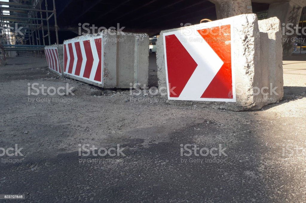 Signs of the direction of detour on concrete blocks stock photo