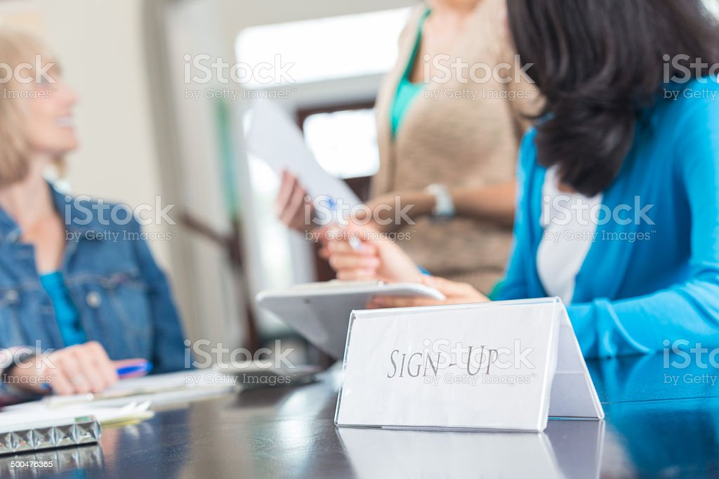 Sign-Up sign on desk with diverse women in background stock photo