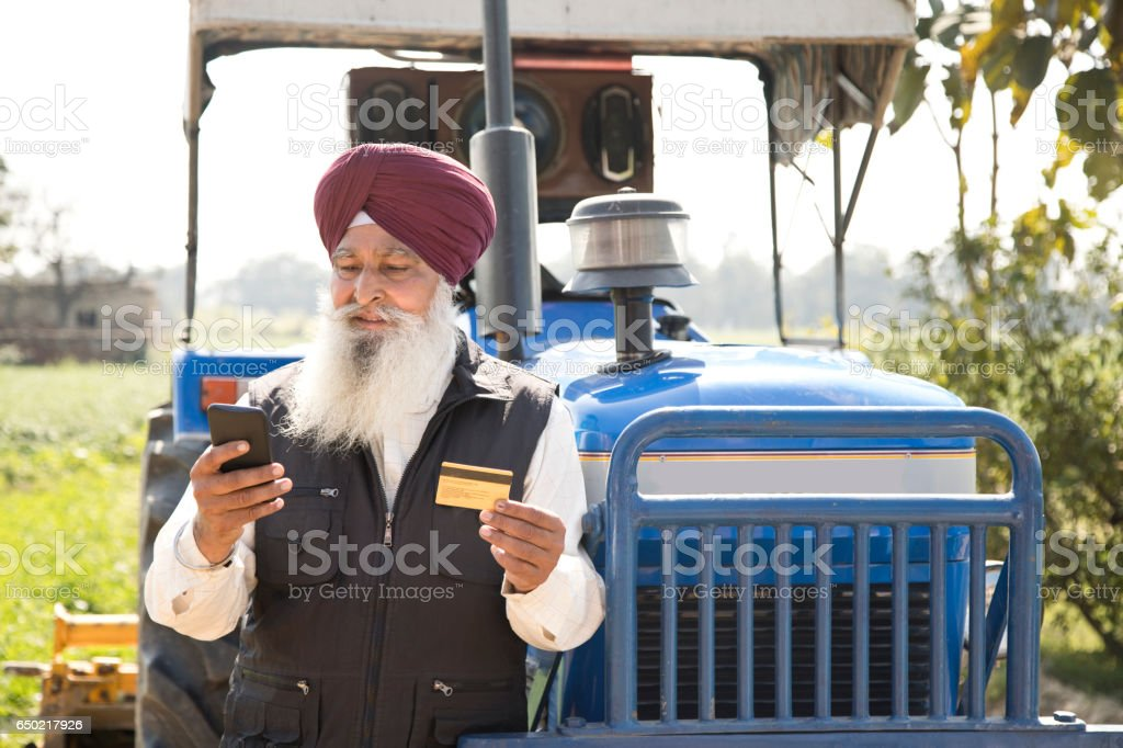 Sikh farmer using credit card and mobile phone stock photo