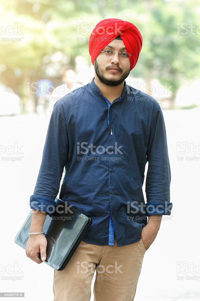 Sikh man holding laptop stock photo