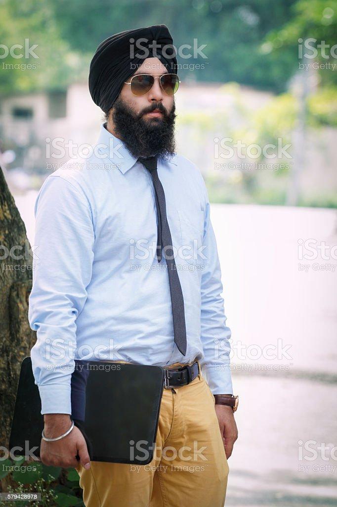 Sikh man holding laptop stock photo
