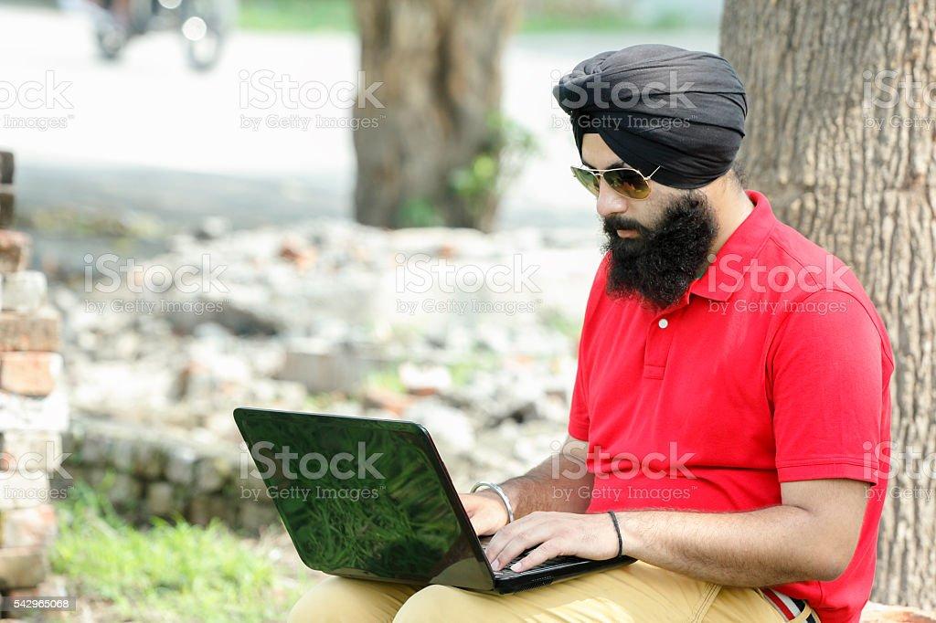 Sikh man using laptop stock photo