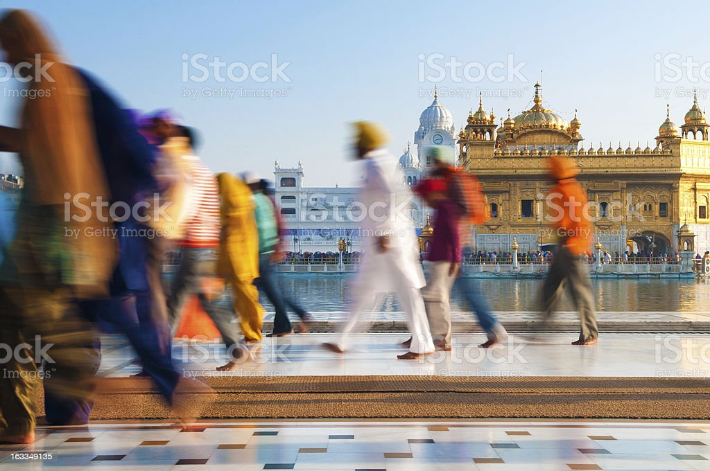 Sikh pilgrims walking past Golden Temple in India stock photo