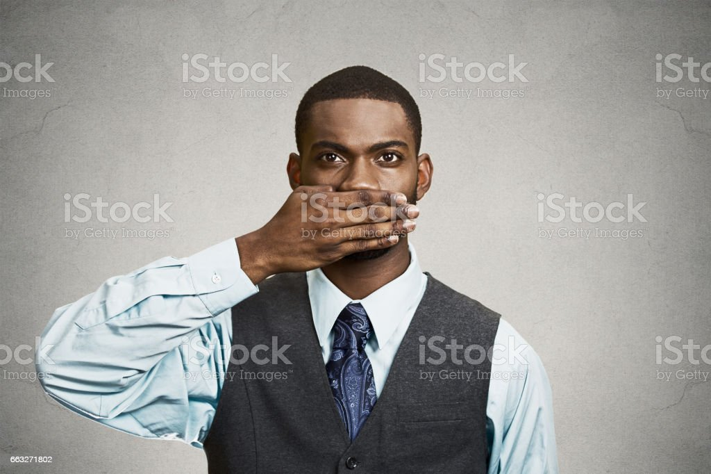 silent young business man covering closed mouth observing stock photo