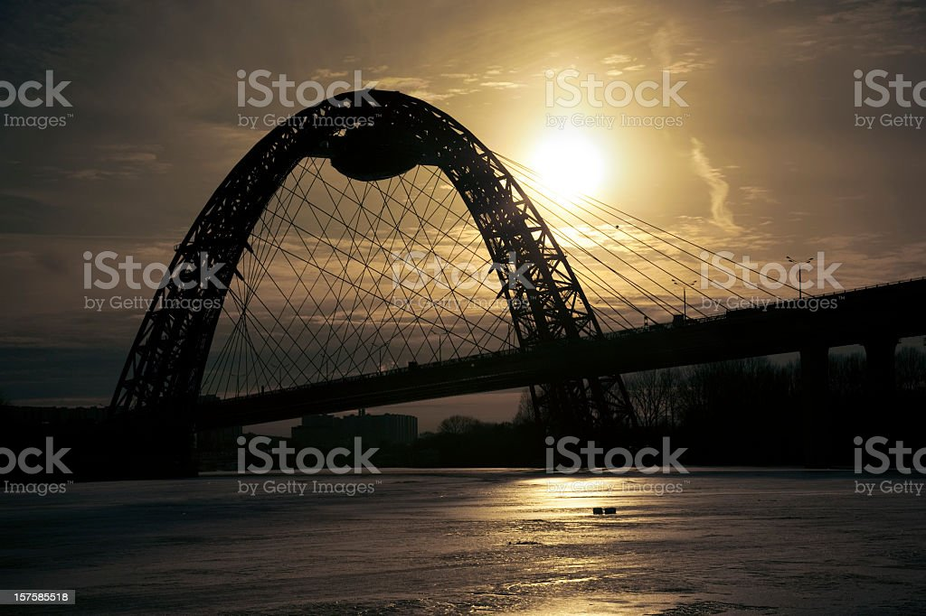 Silhoette of bridge over frozen river at sunset royalty-free stock photo