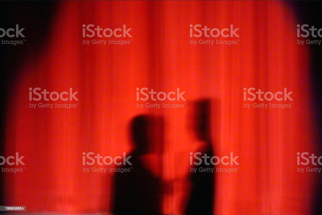silhouette 2 people shadows on red curtain royalty-free stock photo