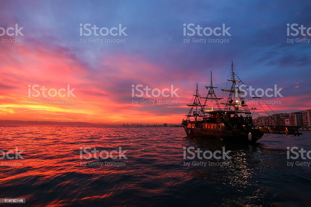 Silhouette an antique ship at a beautiful sunset. stock photo