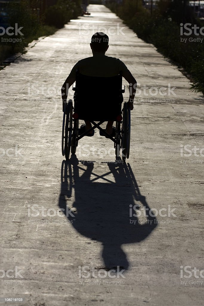 Silhouette And Shadow Of Man On Wheelchair,Outdoor Shot royalty-free stock photo
