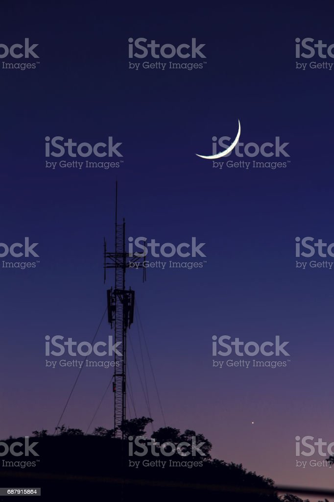 Silhouette antenna and the moon with twilight sky background landscape stock photo