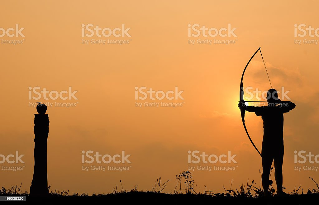 Silhouette archery shoots a bow at an apple on timber stock photo