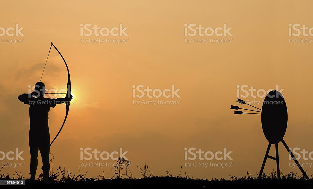 Silhouette archery shoots a bow at the target. stock photo