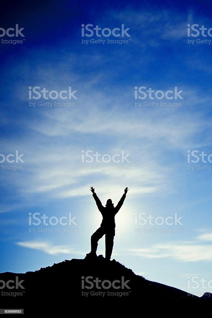 woman silhouetted on pinnacle, arms raised high into the sky stock photo