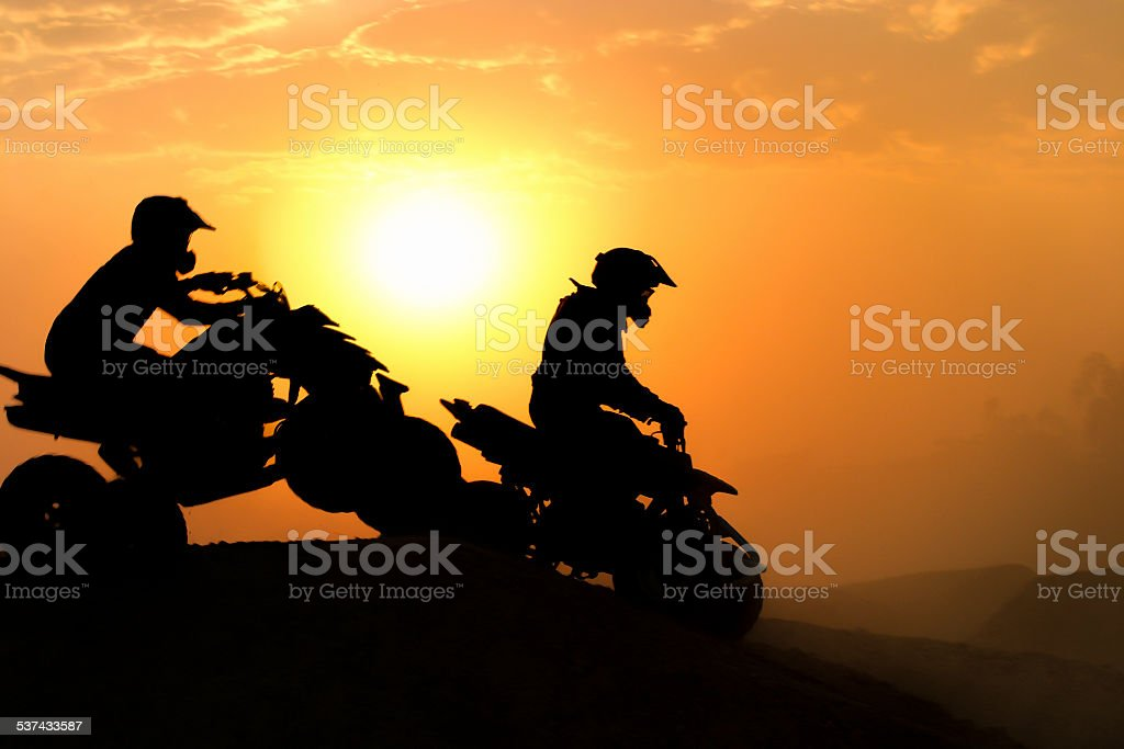Silhouette ATV or Quad bikes Jump in the sunset. stock photo