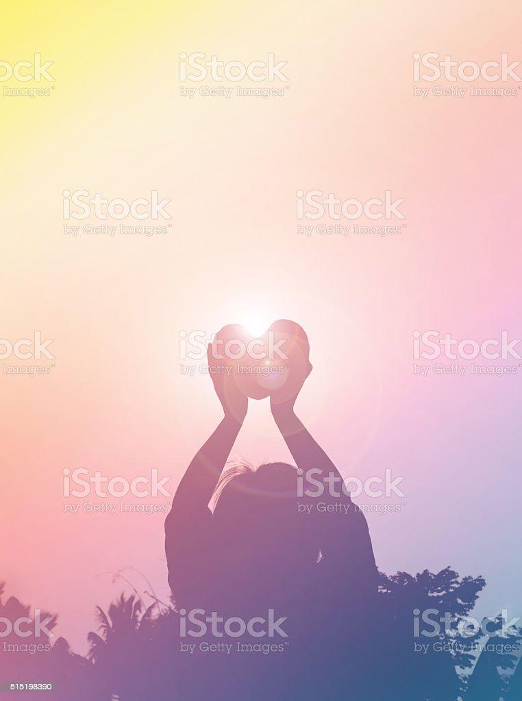 Silhouette back of women raise haert to sky in twilight stock photo