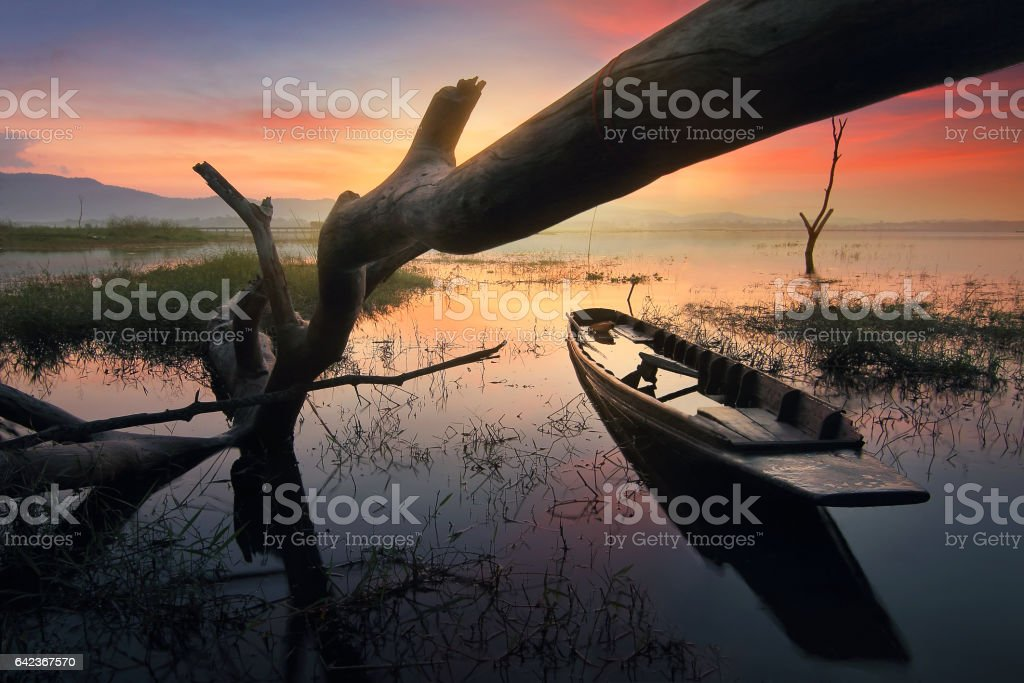 Silhouette beautiful scenery of nature and wreck fishing boats moored beached on the beach during sunrise time and the colorful sky at Bang Pra Reservoir , Chonburi province in Thailand stock photo