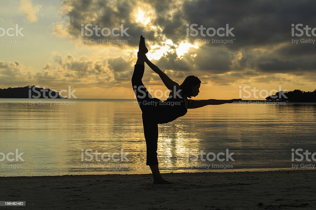 Silhouette  beautiful yoga girl at sunrise on the beach royalty-free stock photo