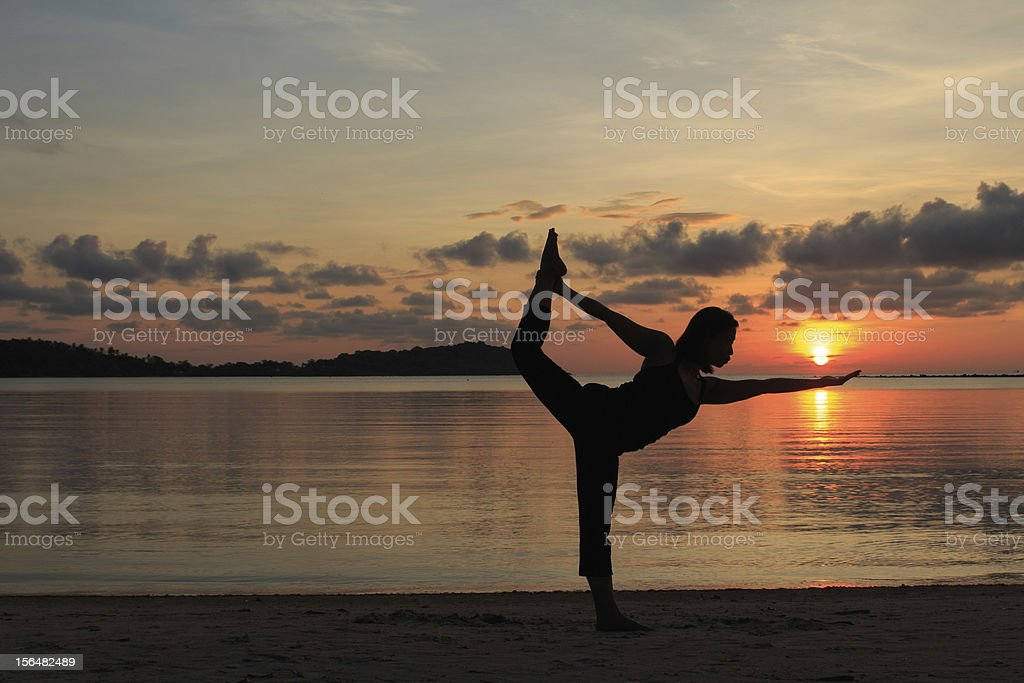 Silhouette  beautiful yoga girl at sunrise on the beach, royalty-free stock photo