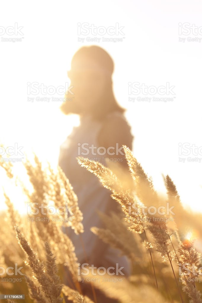 silhouette Beautiful young woman in white dress stock photo