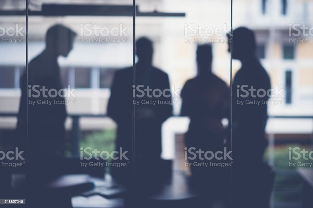 A photo of silhouette business people in meeting room. Male and...