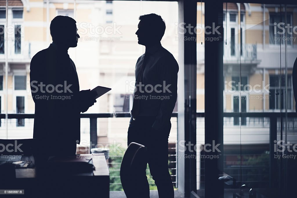 Silhouette businessmen discussing in dark office stock photo