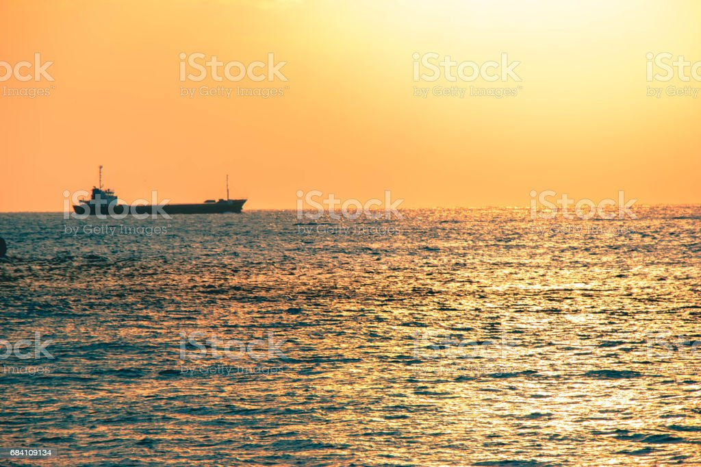 Silhouette cargo ship at the horizontal skyline with Sunset at Akashi Kaikyo Bridge in Kobe, Japan. stock photo