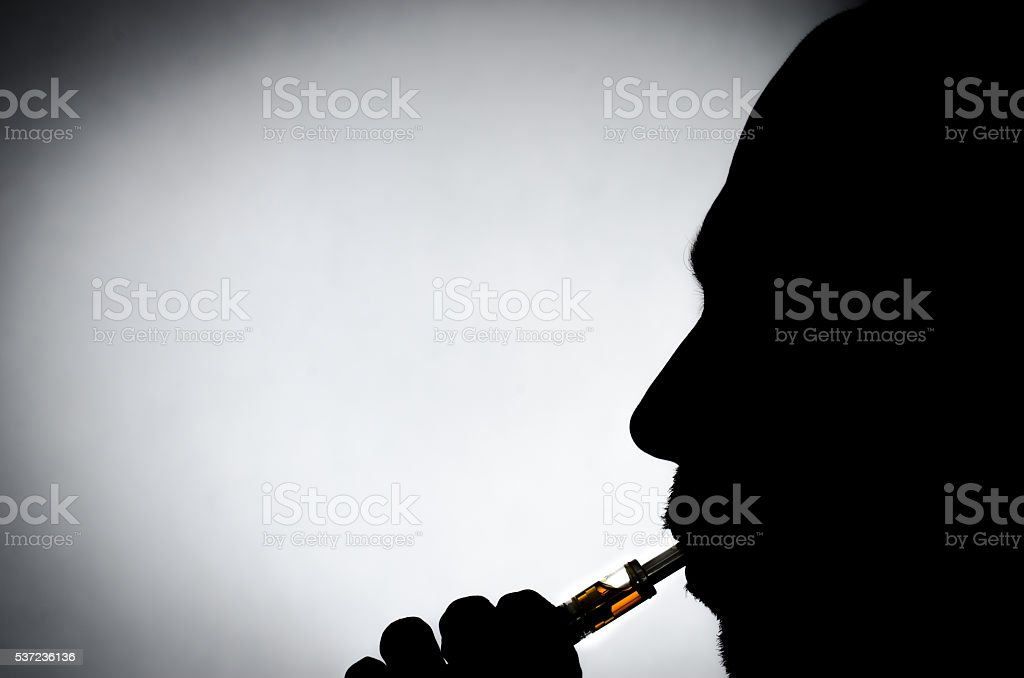 Silhouette close up of man vaping stock photo