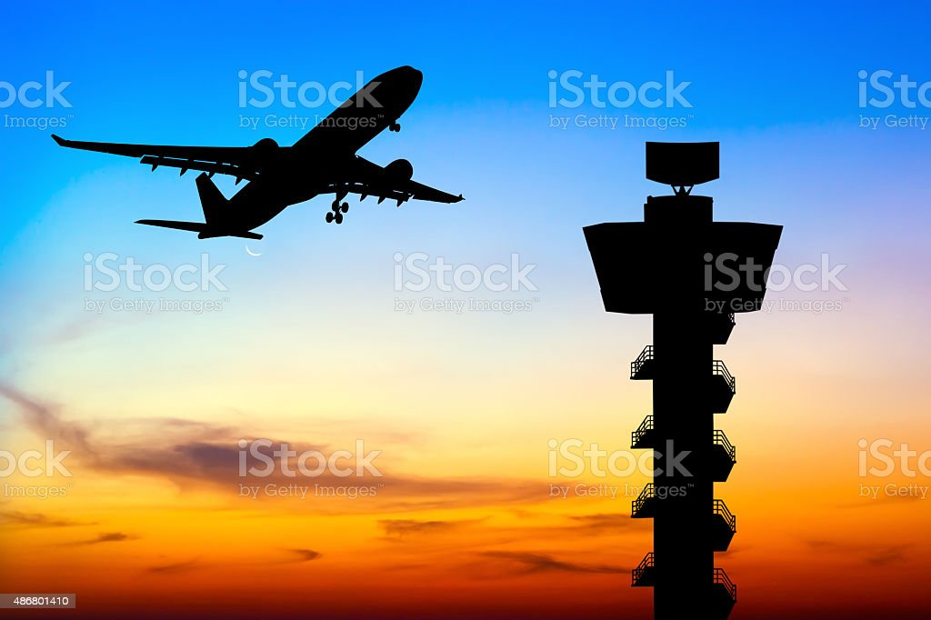Silhouette commercial airplane take off over airport control tow stock photo