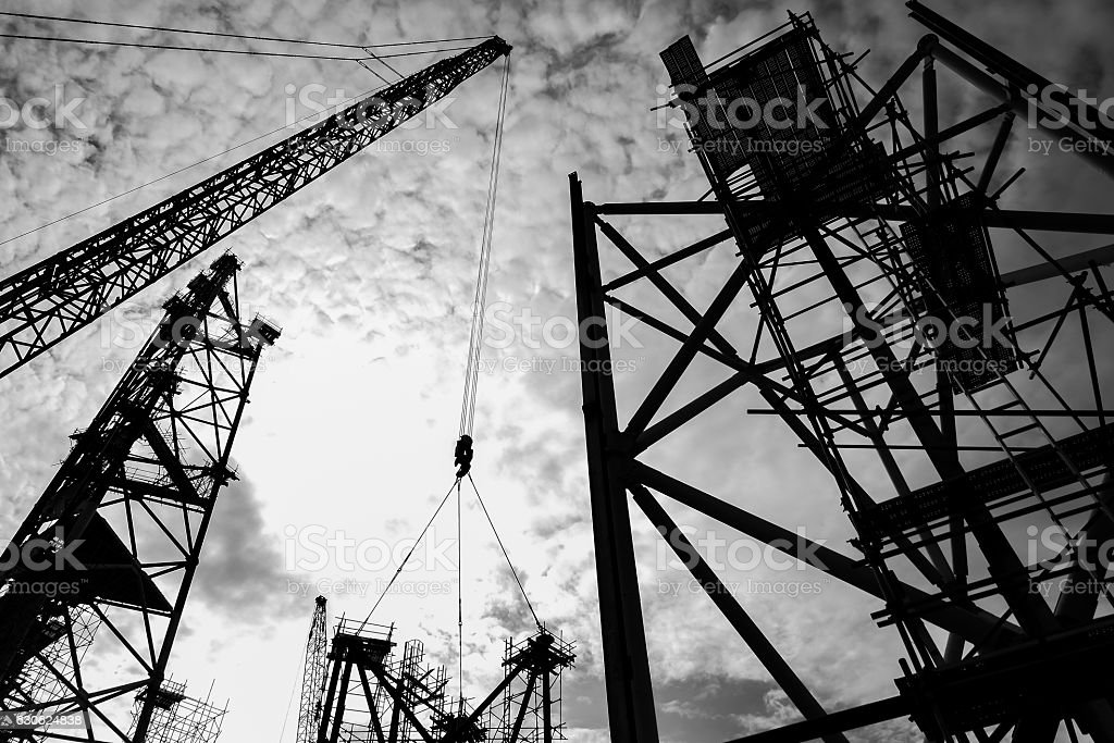 Silhouette construction sites with ringer cranes and scaffolding. stock photo