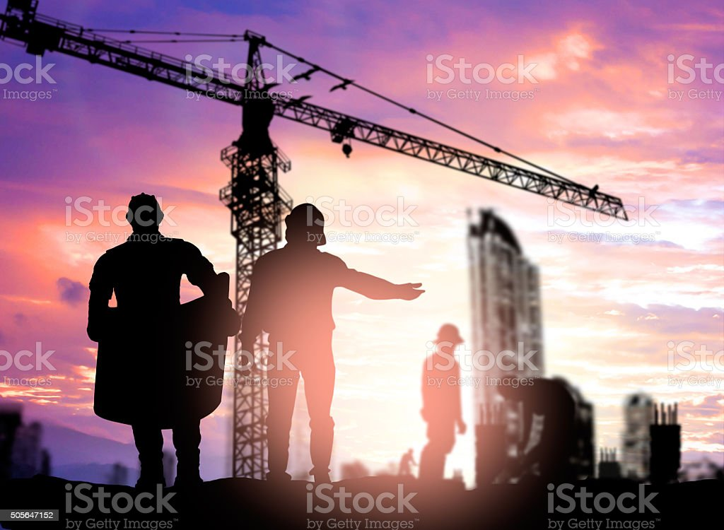 Silhouette engineer looking construction worker under tower cran stock photo