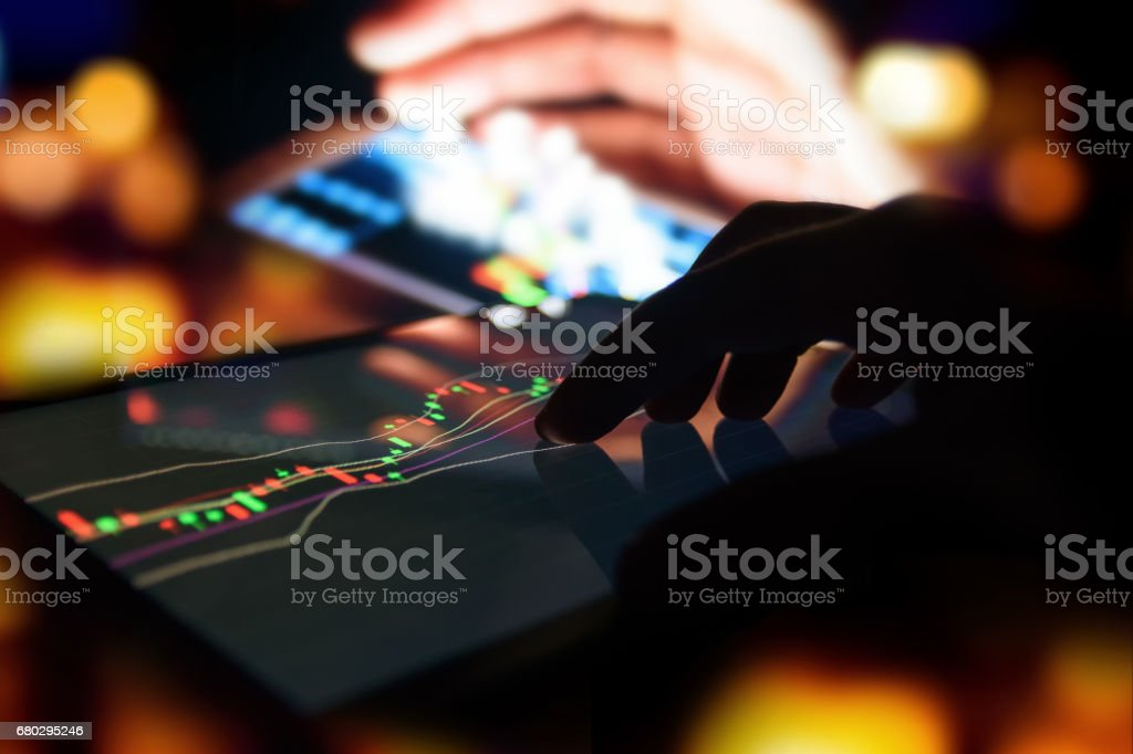 Silhouette finger on tablet with graph stock market trading screen with abstract blur smartphone bokeh background , stock market concept stock photo