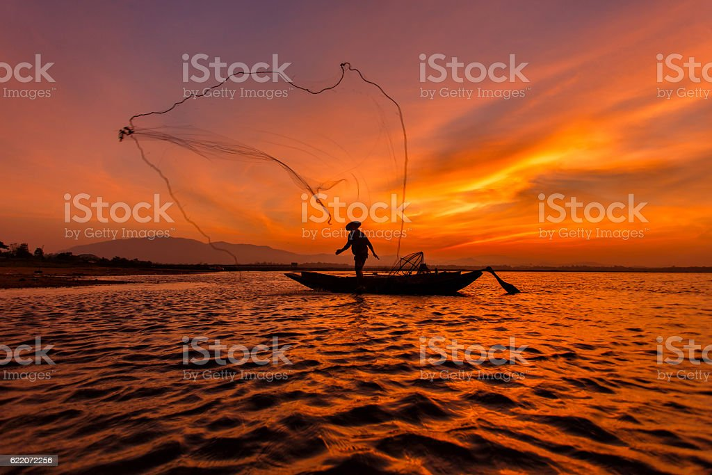 Silhouette fisherman with net at the lake in Thailand stock photo