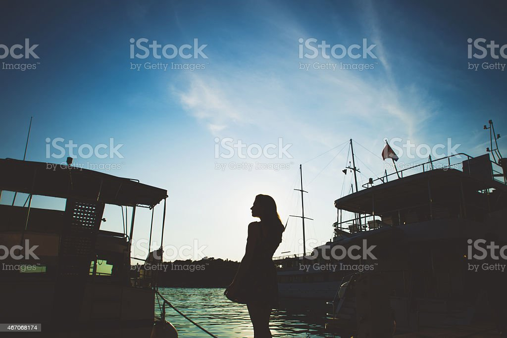silhouette girl and ships on the sea stock photo