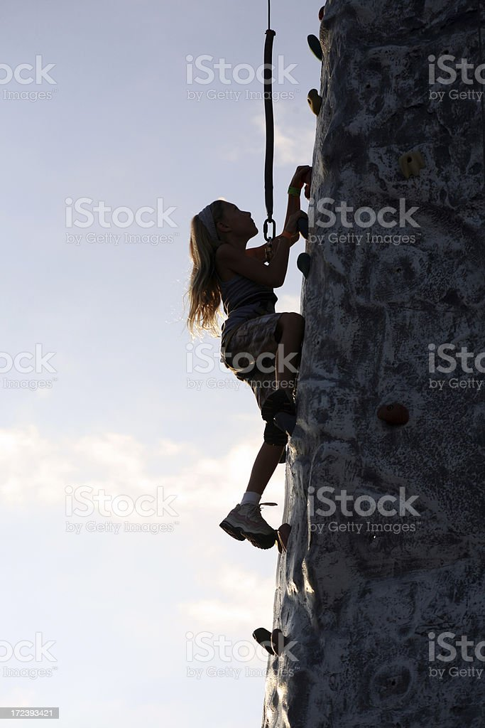 Silhouette Girl climbs rock wall at Festival royalty-free stock photo