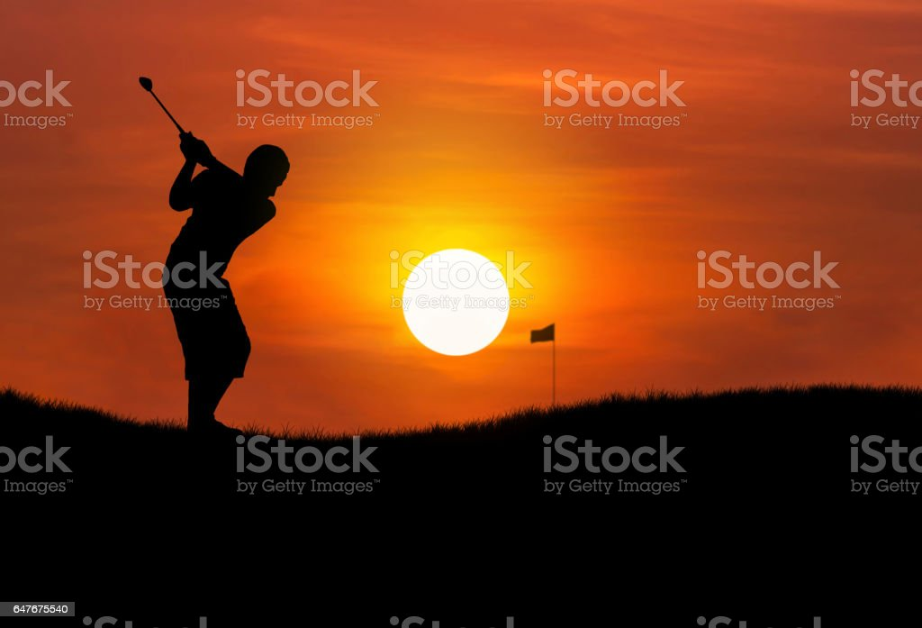 silhouette golfer hitting golf ball at sunset stock photo