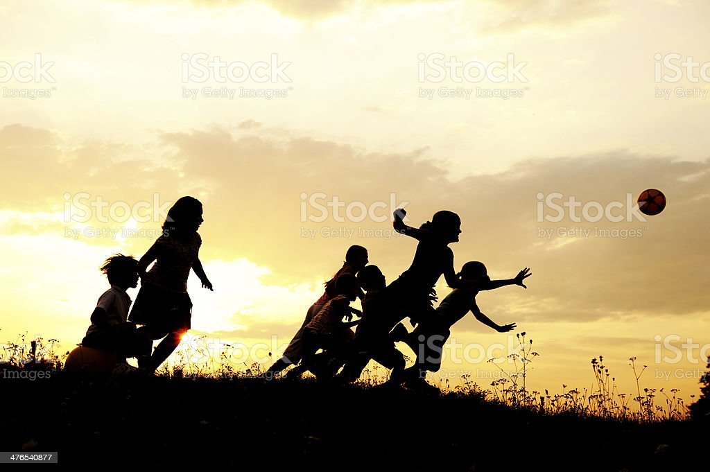 Silhouette, group of happy children playing on meadow, sunset, summertime royalty-free stock photo