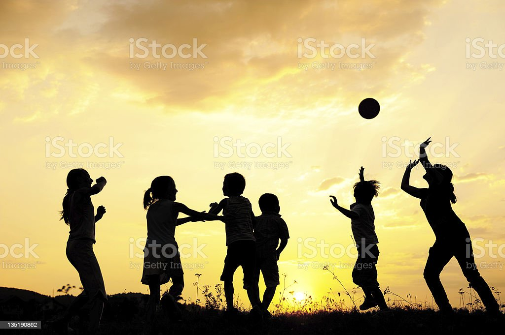 Silhouette, group of happy children playing on meadow, sunset, s stock photo